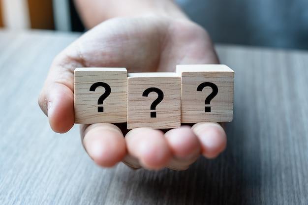 Mano de hombre de negocios con palabra de signo de interrogación (?) con cubo de madera Foto Premium
