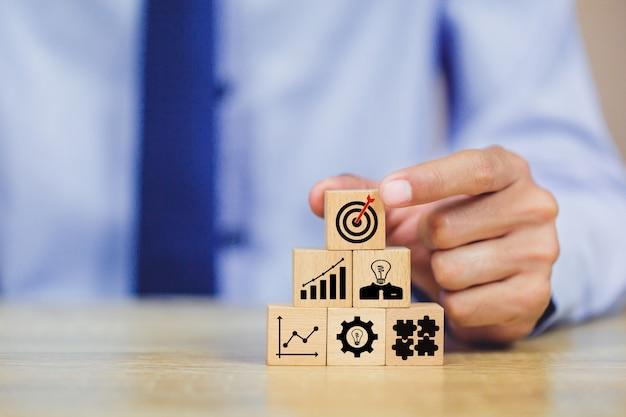 Mano del hombre de negocios que arregla el bloque de madera con estrategia empresarial de la blanco del icono. Foto Premium