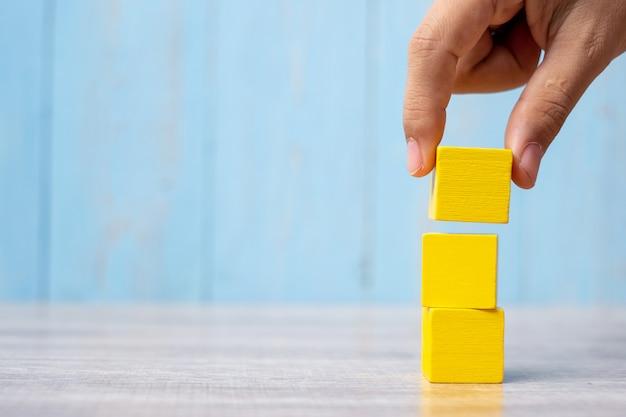 Mano del hombre de negocios que coloca o que tira del bloque de madera en el edificio. planificación empresarial, gestión de riesgos, solución, estrategia, diferente y única Foto Premium