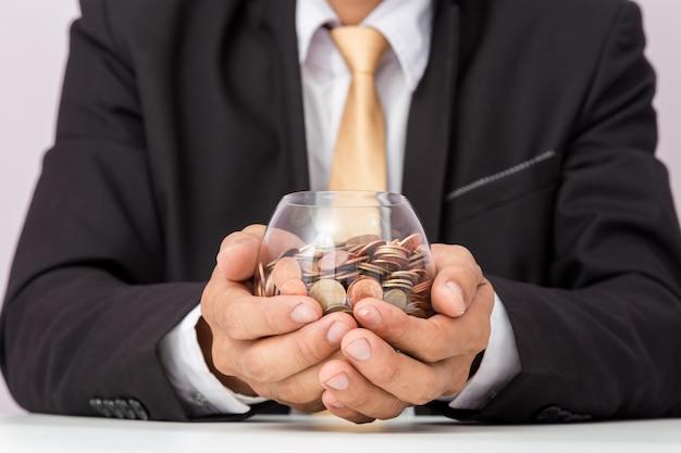 Mano del hombre de negocios que pone las monedas en el vidrio, concepto de ahorrar dinero para la contabilidad de las finanzas Foto Premium