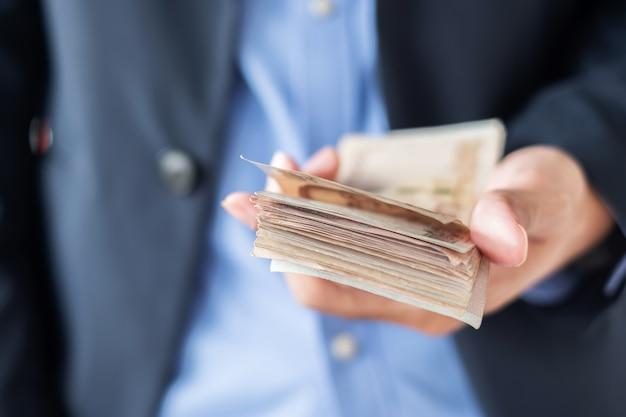 Mano del hombre de negocios que sostiene la pila del billete de banco del baht tailandés. Foto Premium