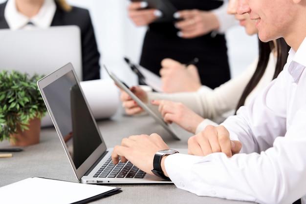 La mano del hombre de negocios sonriente usando el ordenador portátil que se sienta con su colega en el escritorio Foto gratis