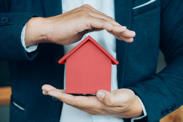 Mano de hombre de negocios sostenga el modelo de casa ahorrando pequeña casa. Foto gratis