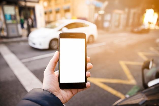 La mano del hombre que muestra el teléfono móvil con pantalla en blanco en la carretera Foto gratis