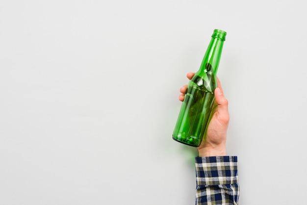 Mano del hombre que sostiene la botella de vidrio Foto gratis