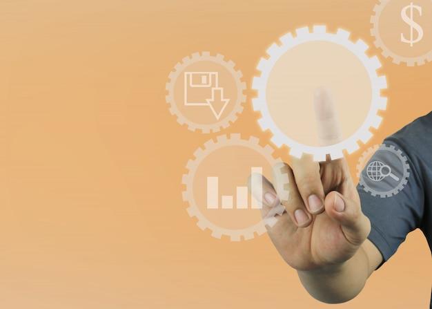 La mano del hombre señala al engranaje circular vacío en fondo anaranjado del color. Foto Premium