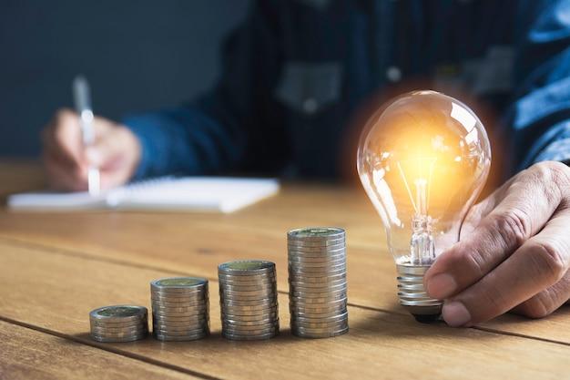 Mano de hombre sosteniendo una bombilla con pila de monedas y espacio de copia Foto Premium