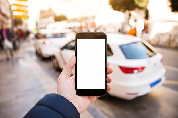 La mano del hombre sosteniendo el teléfono móvil frente al tráfico en la carretera Foto gratis