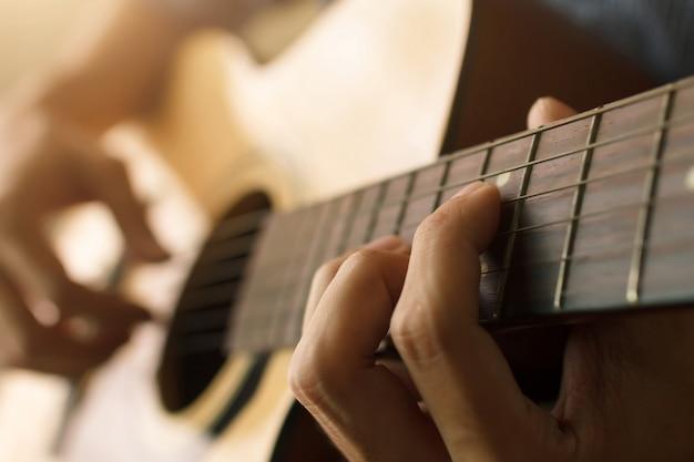 La mano del hombre tocando la guitarra acústica, concepto musical Foto Premium