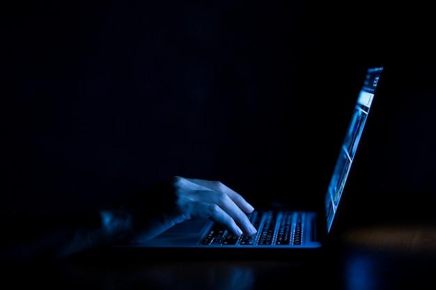 Mano de un hombre usando una computadora portátil en la oscuridad Foto Premium