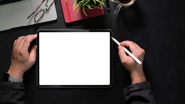 Mano del hombre de la vista superior que sostiene la tableta y los lápices, tableta de dibujo de la pantalla en blanco de la maqueta Foto Premium