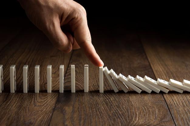 La mano de los hombres detuvo el efecto dominó, sobre una madera marrón. Foto Premium