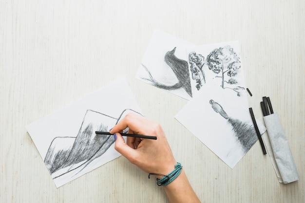 Mano humana dibujando en papel con palillo de carbón cerca de ...