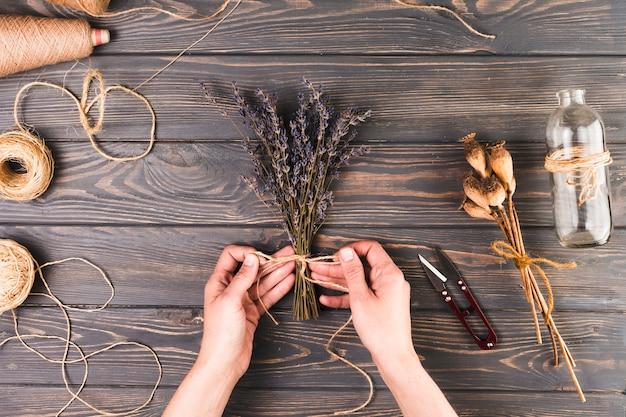Mano humana haciendo un ramo de flores usando una cuerda cerca de una botella de vidrio sobre una mesa con textura Foto gratis
