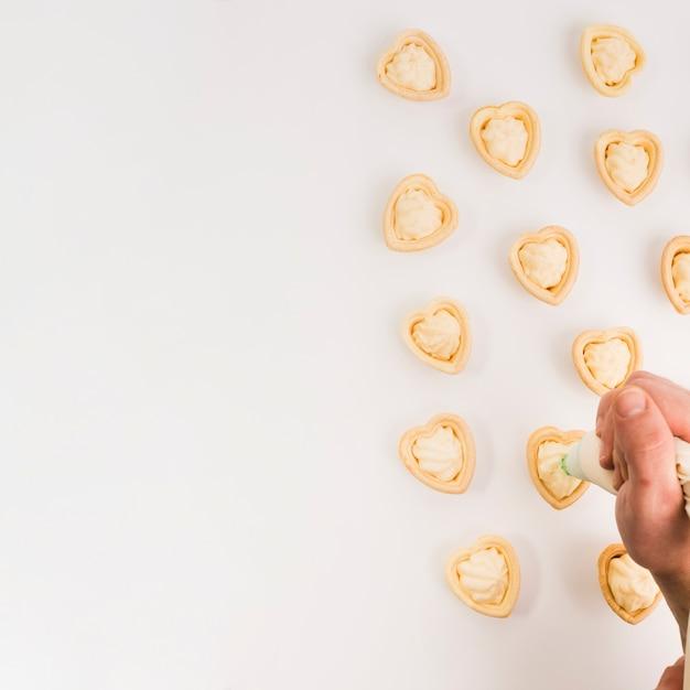 Mano humana poniendo crema fresca en delicioso corazón forma tartaleta Foto gratis