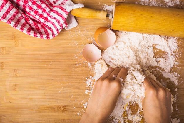 Mano humana que mezcla la harina con el huevo en el escritorio de madera Foto gratis