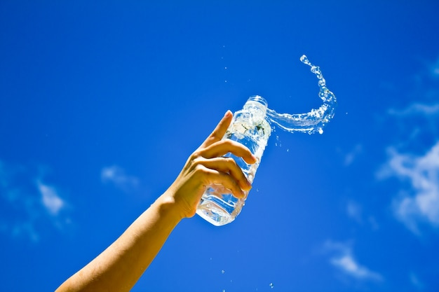Mano humana que sostiene una botella de agua Foto gratis