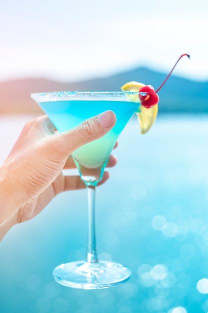 Mano humana está sosteniendo bebida de verano en la playa Foto Premium