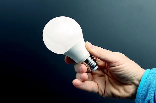 Mano humana sosteniendo la lámpara led incluida en una oscuridad. industria eléctrica y led Foto Premium