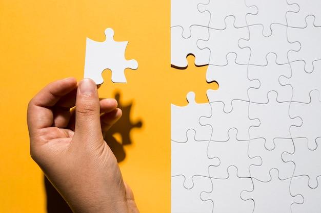 Mano humana sosteniendo una pieza de rompecabezas sobre una cuadrícula de rompecabezas blanca sobre fondo amarillo Foto gratis