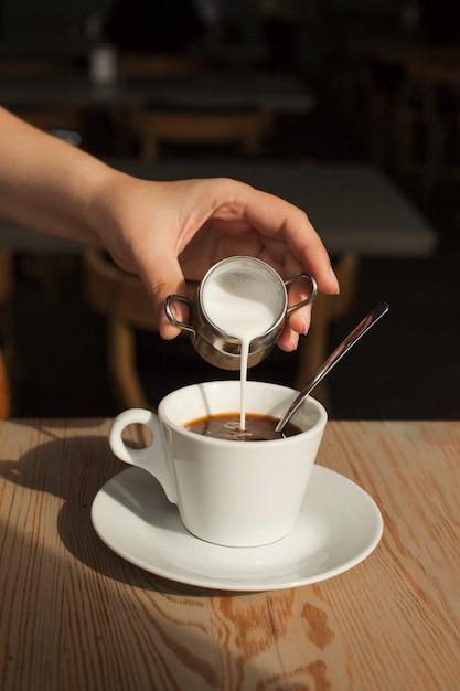 Mano humana vertiendo leche en el café negro en la cafetería Foto gratis