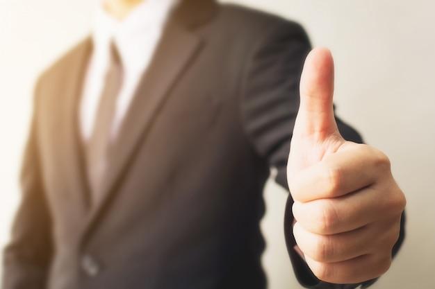 Mano joven del hombre de negocios que muestra el pulgar encima del gesto de la muestra Foto Premium