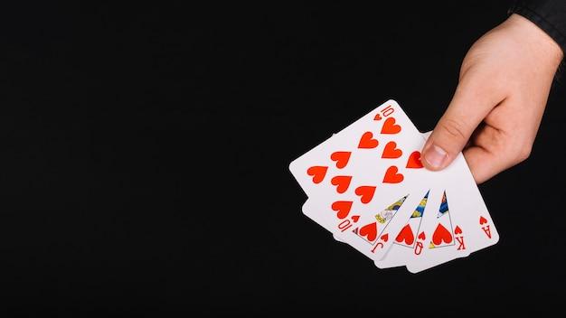 Mano del jugador de póker con corazón de escalera real sobre fondo negro Foto gratis