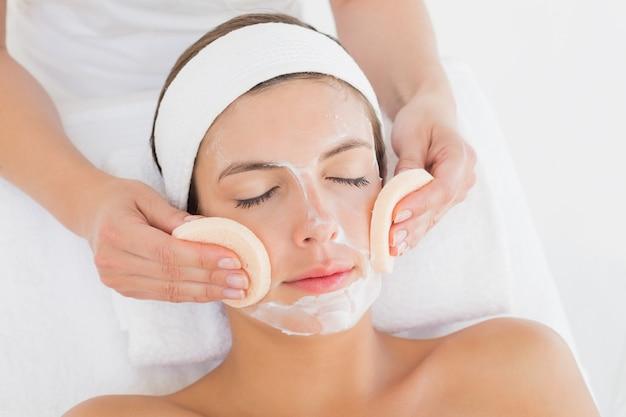Mano limpiando la cara de mujer con hisopos de algodón en el centro de spa Foto Premium
