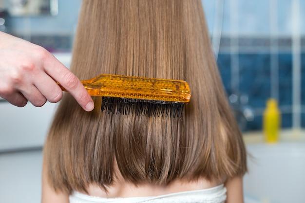Mano de la madre con cepillo peinar el cabello de la niña niño. Foto Premium