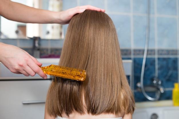 La mano de la madre con un cepillo que peina el cabello largo y rubio de la niña linda después del baño Foto Premium