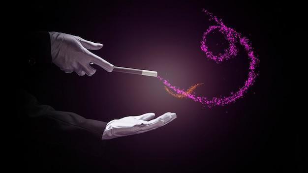 La mano del mago realiza truco con la varita mágica sobre fondo negro Foto gratis