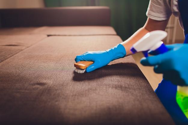 Mano masculina en guantes protectores azules claros que limpian el sofá del sofá Foto Premium