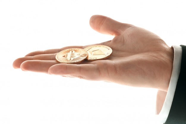Mano masculina con monedas de oro bitcoin Foto gratis