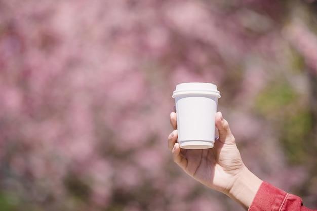 Mano masculina que aparece de una taza blanca de café caliente delante de flor de cerezo rosa Foto Premium