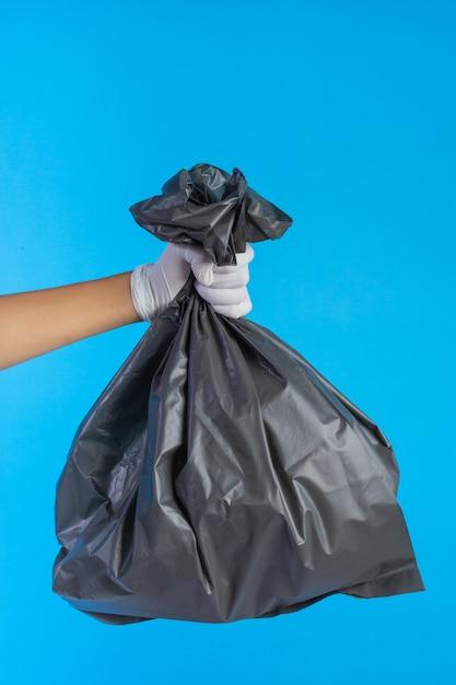 La mano masculina que sostiene una bolsa de basura y un azul. Foto gratis