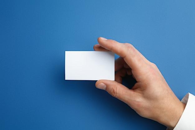 Mano masculina que sostiene una tarjeta de presentación en blanco en la pared azul para texto o diseño. plantillas de tarjetas de crédito en blanco para contacto o uso en negocios. oficina de finanzas. copyspace. Foto gratis