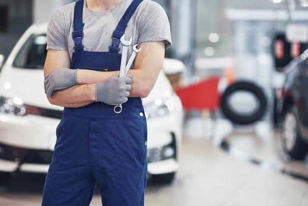 Mano de mecánico con llave. garaje de reparación de automóviles Foto gratis