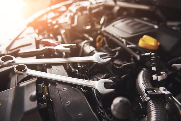 Mano de mecánico revisando y arreglando un automóvil roto en el garaje de servicio de automóviles. Foto gratis