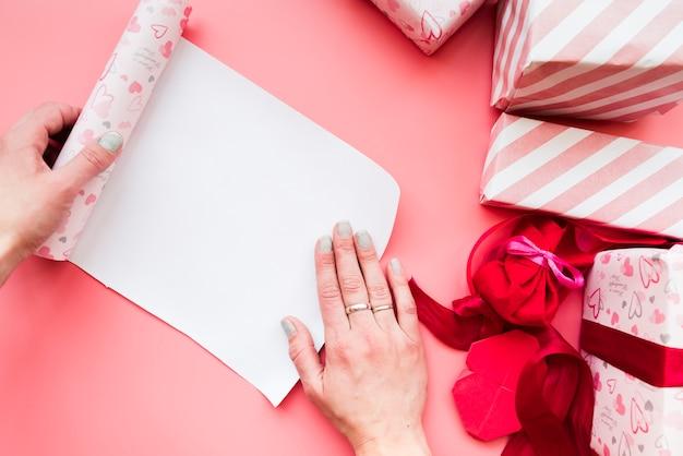 La mano de la mujer abriendo el papel de regalo enrollado con una caja de regalo envuelta en un fondo rosa Foto gratis