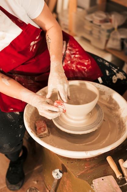Mano de mujer alisando el tazón con herramienta plana en la rueda de alfarero Foto gratis
