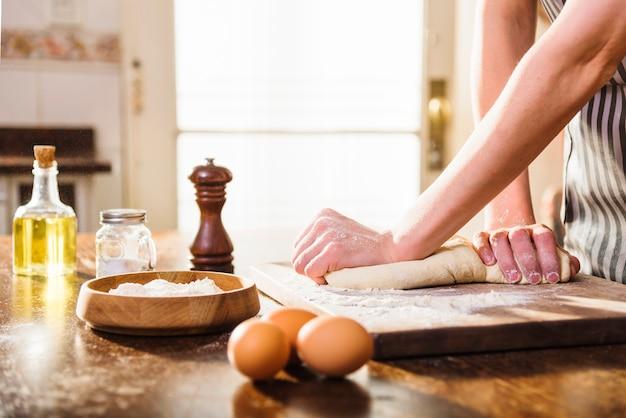 Mano de mujer amasando masa con ingredientes en mesa de madera Foto gratis