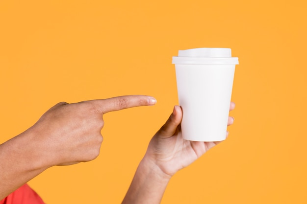 Mano de mujer apuntando sobre vaso desechable en superficie coloreada Foto gratis