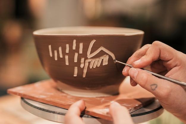 Mano de mujer artesana decorando el bol con herramienta. Foto gratis