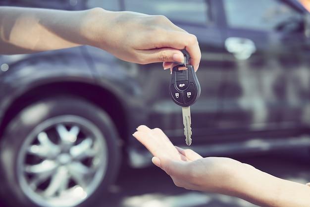 La mano de la mujer da la llave del coche y el fondo borroso. Foto Premium