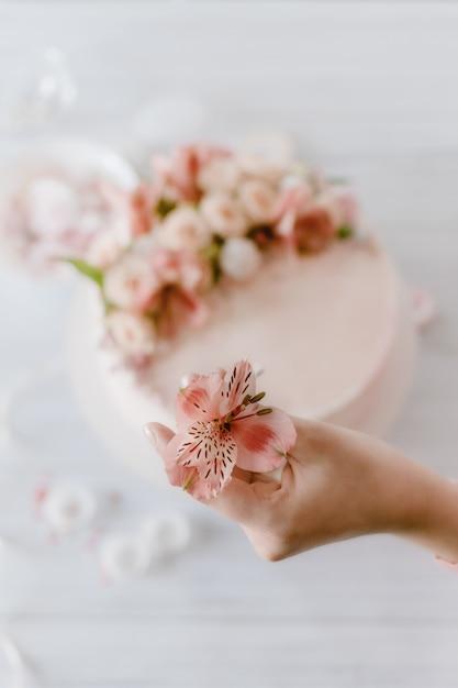 Mano de mujer decora el pastel de cumpleaños de boda rosa con flores frescas. Foto Premium