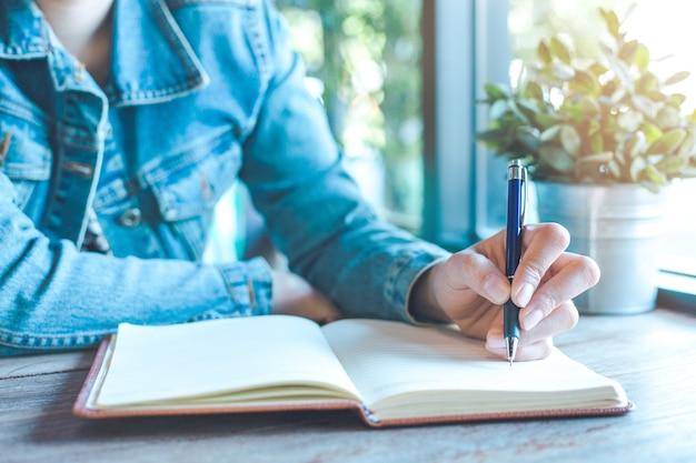 La mano de la mujer está escribiendo en el cuaderno con una pluma en la oficina Foto Premium