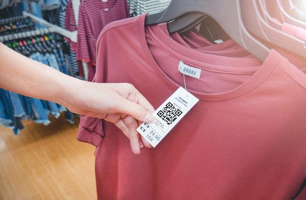 La mano de la mujer con una etiqueta de etiqueta colgante de tela con código qr en una tienda de ropa. Foto Premium