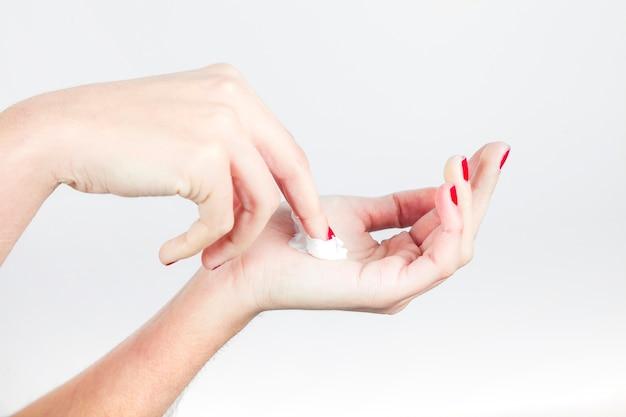 La mano de la mujer hermosa con la crema aislada en el fondo blanco Foto gratis