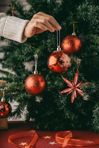 Mano de mujer irreconocible con adorno delante del árbol de navidad Foto gratis