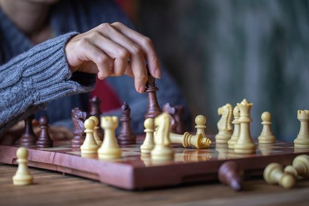 Mano de mujer joven jugando al ajedrez para el concepto de ganador de concurso de desafío empresarial Foto Premium